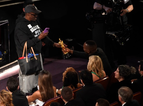 "Mahershala Ali, right, hands his award for best actor in a supporting role for ""Moonlight"" to a tourist named Gary during the Oscars on Sunday, Feb. 26, 2017, at the Dolby Theatre in Los Angeles. (Photo by Chris Pizzello/Invision/AP)"